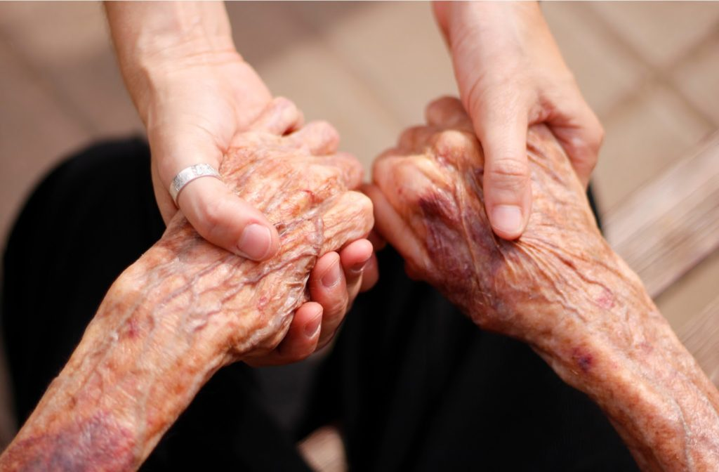 Daughter holding both of senior mothers hand while sitting down
