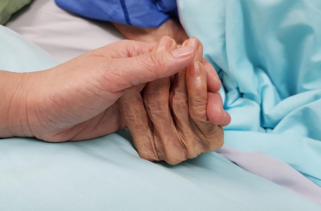 Daughter holding senior mothers hand at nursing care